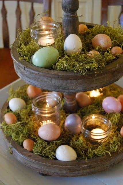 a wooden cupcake stand covered with moss, dyed eggs and with candles