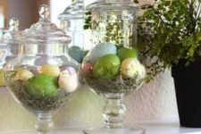 21 half-dozen faux Easter eggs in pastel colors placed in apothecary jars and lined with straw