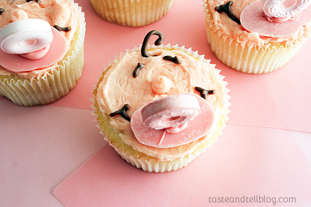 DIY pink vanilla cupcakes with baby faces and pacifiers (via www.tasteandtellblog.com)