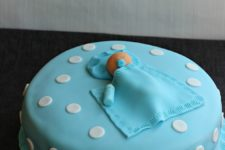 DIY baby shower cake with a baby sleeping on top