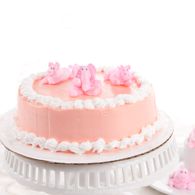 DIY pink baby shower cake with piglets and elephants (via bobbiesbakingblog.com)
