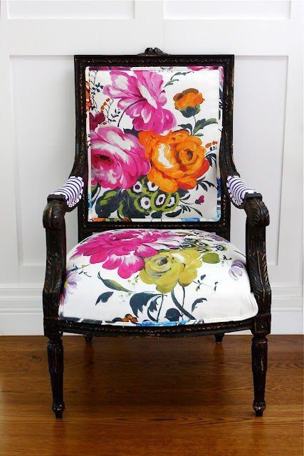 a gorgeous vintage armchair with black framing and white upholstery plus super bold flowers