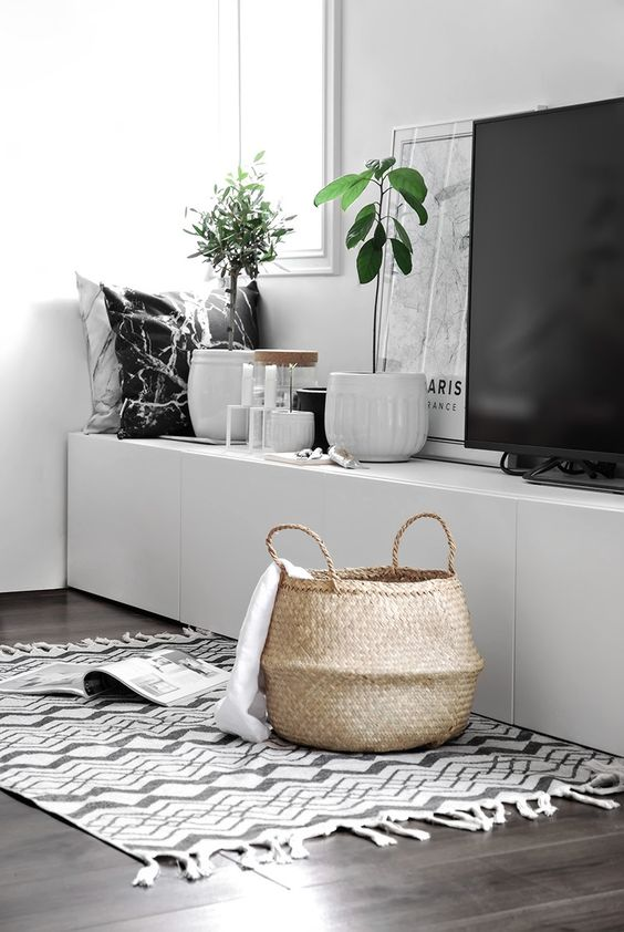 a basket with handles in the living room may be used for pillows or blankets