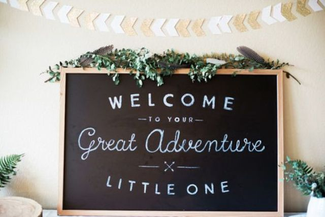a chalkboard sign decorated with fresh greenery