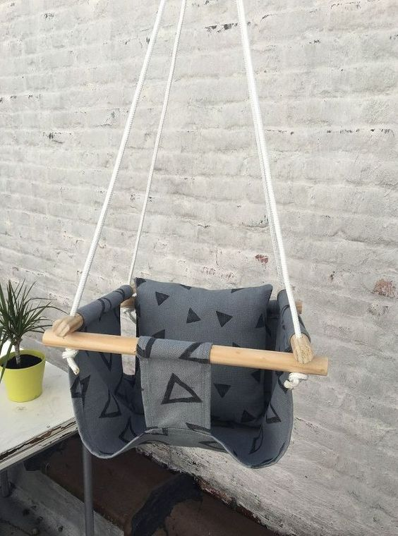a comfy fabric and wooden stick baby swing with a pillow