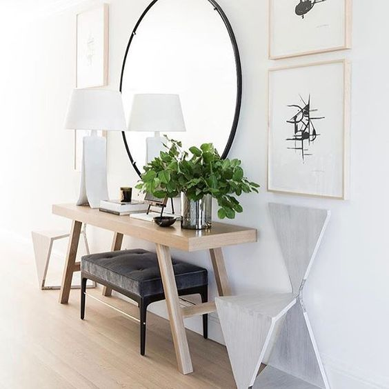 a large round mirror in a black frame is a gorgeous modern idea