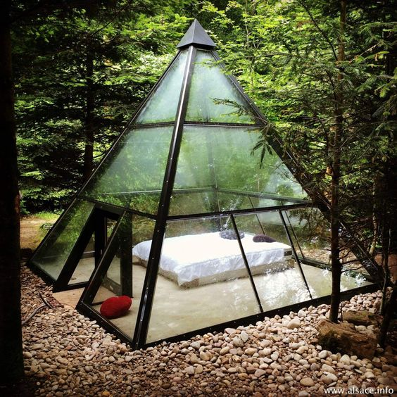 a metal and glass pyramid with a bed inside to enjoy the views around and merge with nature