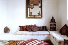 04 a Moroccan space with printed pillows and a rug and a large refined mirror
