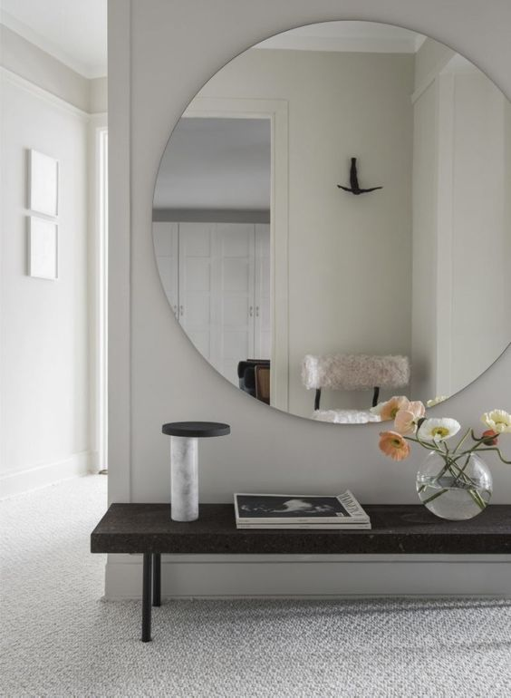a large scale minimalist round mirror with no frame looks fresh