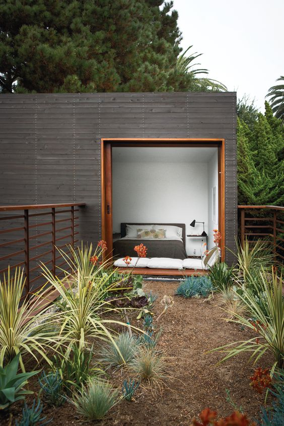 a modern small house in your garden covered with dark wood