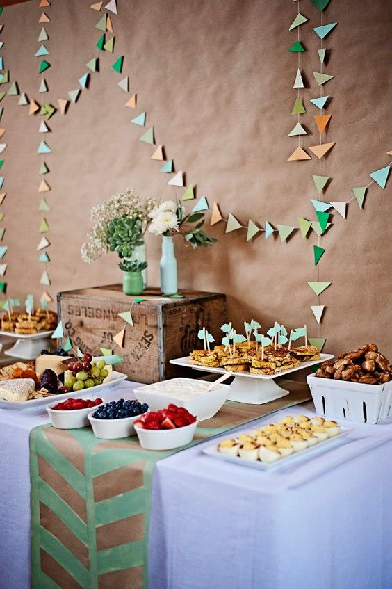 colorful triangle garlands over the dessert table for a vintage shower