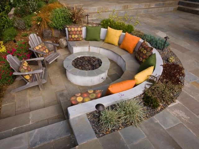 sunken conversation pit with a fire pit and colorful pillows for an inviting look