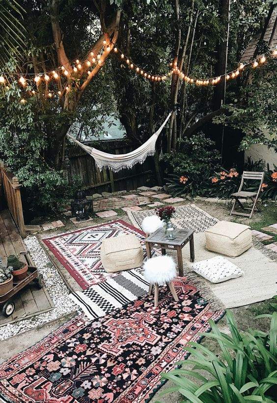 a boho Moroccan outdoor space with printed rugs and ottomans