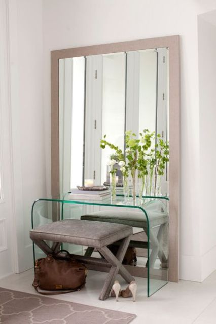 a mirror in a light colored wooden frame for a modern entryway
