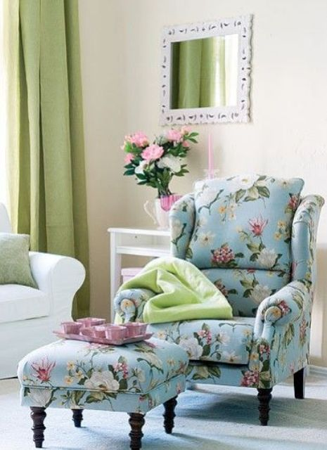 blue armchair with a footrest and pink and white flower prints