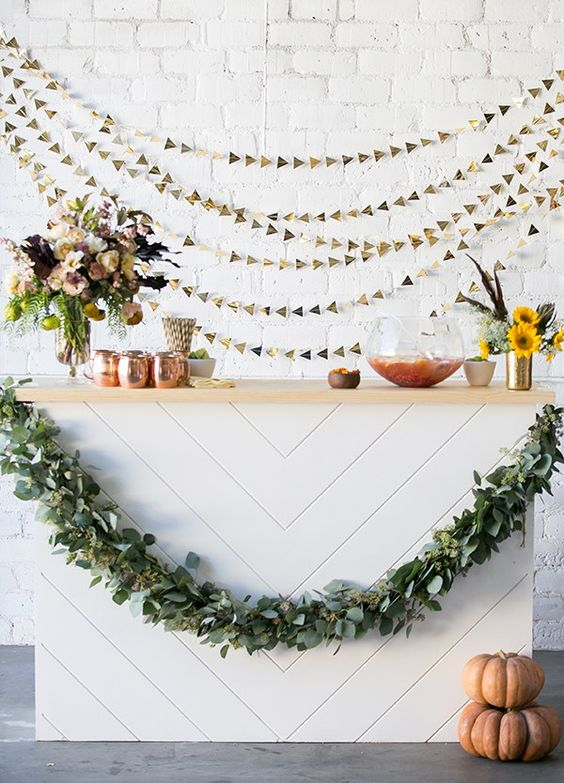 metallic gold triangle garlands as a backdrop for the bar