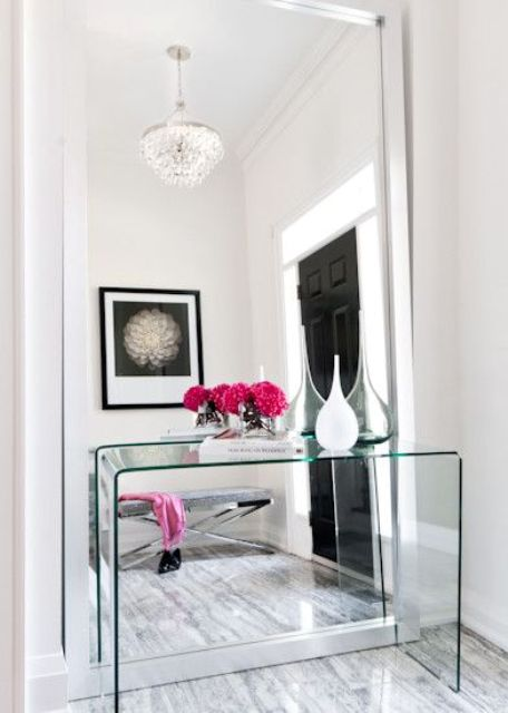 a modern mirror with no frame takes the whole wall and a glass console complements the look