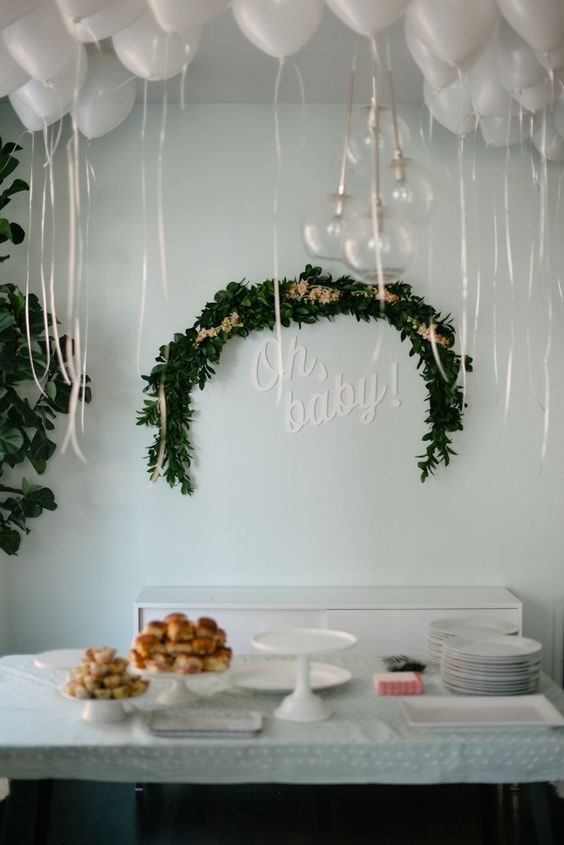a half moon greenery wreath and white balloons create a heavenly atmosphere