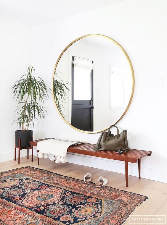 a large scale round mirror in a gilded frame adds a glam feel