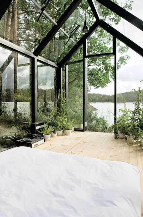 a small metal and glass house placed on a lake shore to enjoy the views