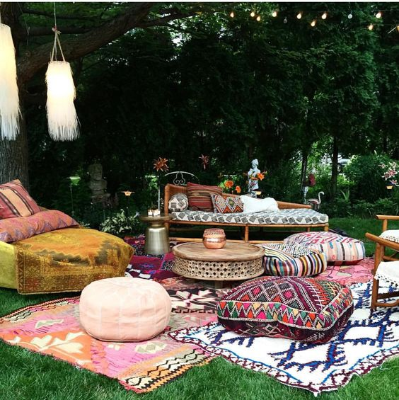 a boho lounge with printed rugs, ottomans and upholstery and tassels hanging