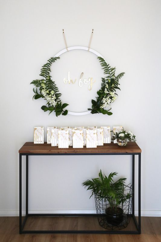 a modern greenery wreath with white blooms and a potted planter for favor table decor