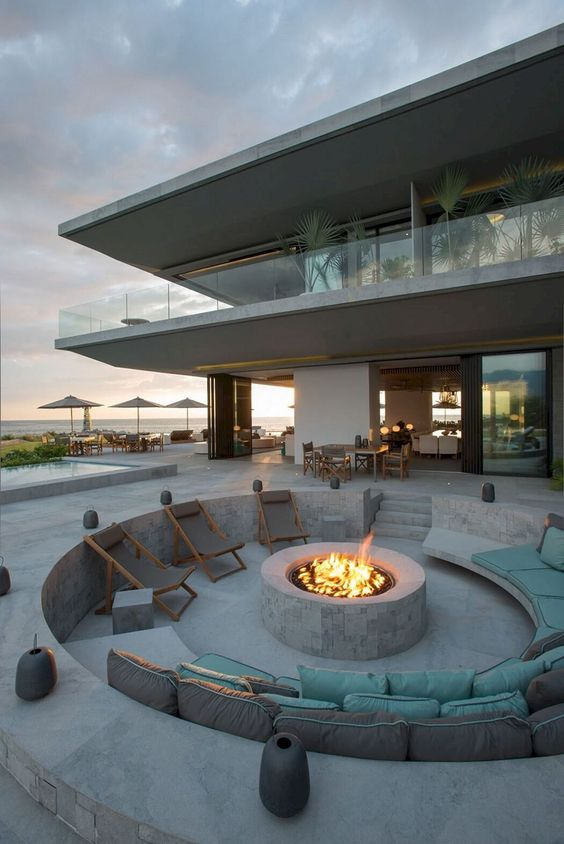 round sunken stone conversation pit with a fire, folding chairs and a stone bench