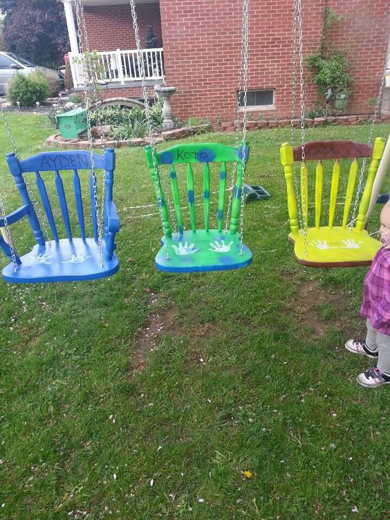 several swings of old chairs painted bright and hung on chains
