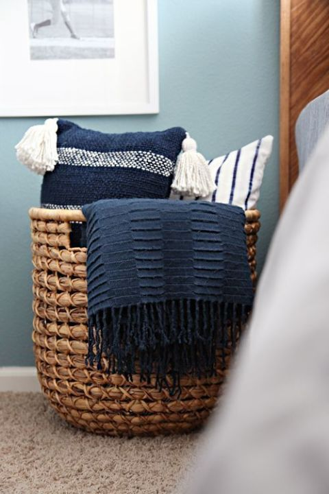 a large basket with handles to store throw pillows and blankets in the bedroom