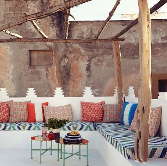 bold printed textiles on white and low tables look very Moroccan-inspired
