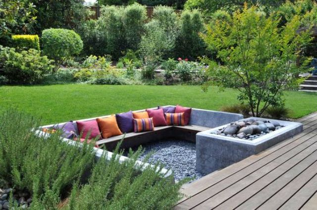 a sunken conversation pit done in concrete and with pebbles and colorful pillows