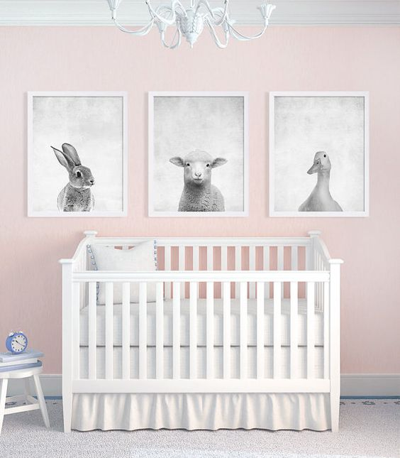 a set of three animal prints in black and white contrasts with the pink walls