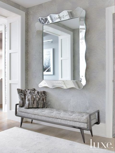 large mirror in a silver ruffled frame for a feminine entryway