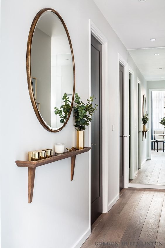 oversized mirror in a wooden frame and a matching shelf