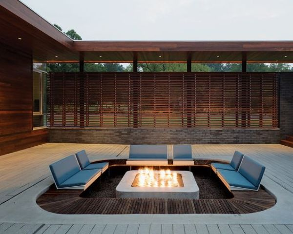 a modern conversation pit with a fire in the center and attached seats