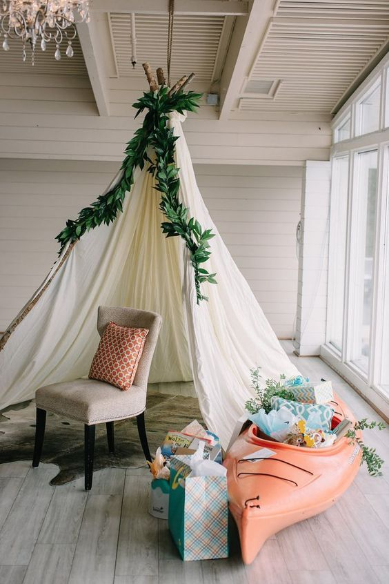 a teepee topped with greenery for a boho shower