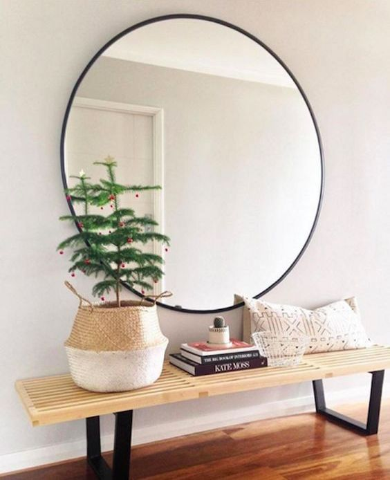 oversized round mirror in a black frame over the bench for a modern look