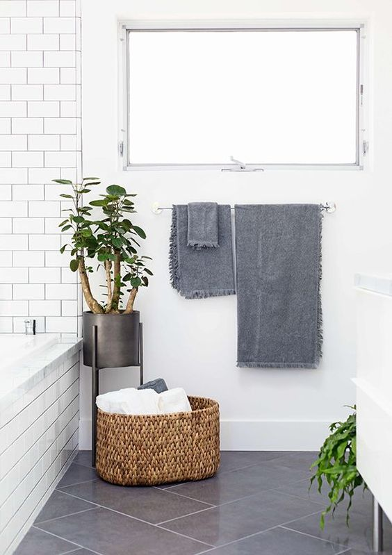 a basket in a bathroom adds a textural touch and interest