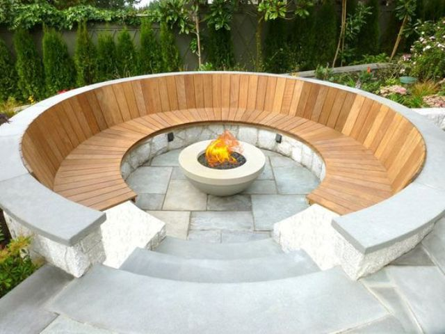 a modern stone and warm-colored wood round conversation pit with a fire