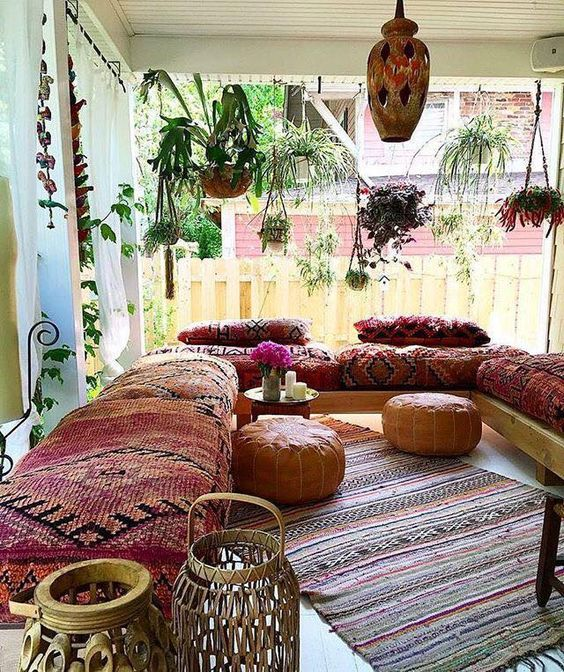 outdoor lounge with bold upholstery furniture and rugs and traditional ottomans and lanterns