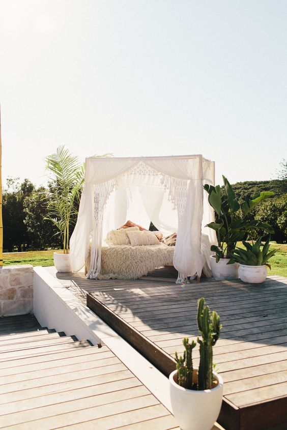 a boho-styled outdoor bedroom under a canopy may be enough to relax and to protect you from the sun