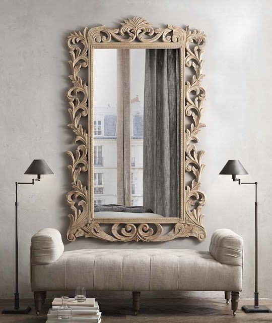 a mirror in a carved wooden frame with vignettes