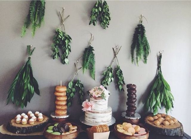 bunches of greenery over the dessert table look chic for a boho shower
