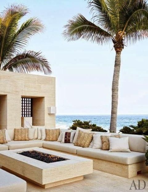 coastal stone conversation pit with a modern fireplace and pillows and a sea view
