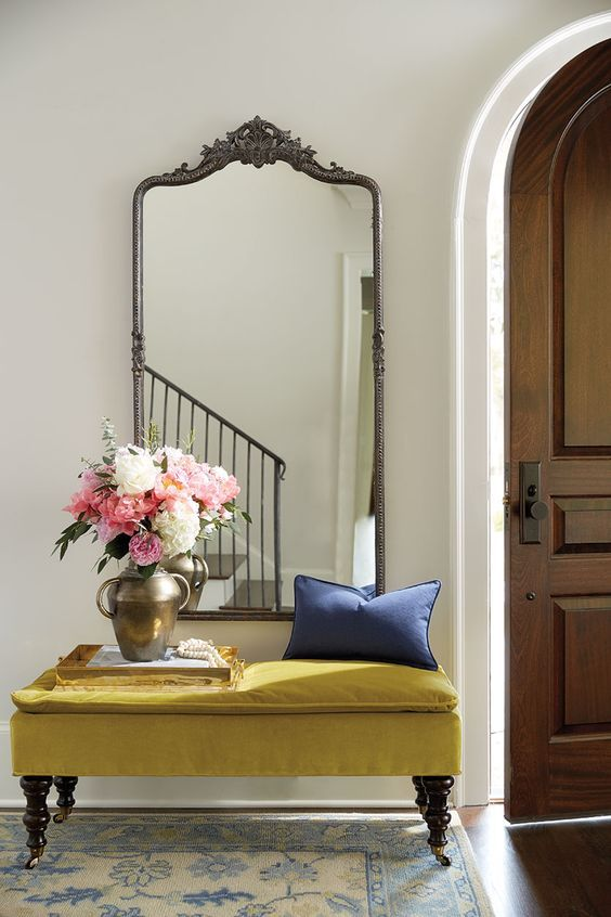 a vintage mirror in a metal frame over the upholstered bench