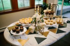 16 black and gold triangles placed on a dessert table