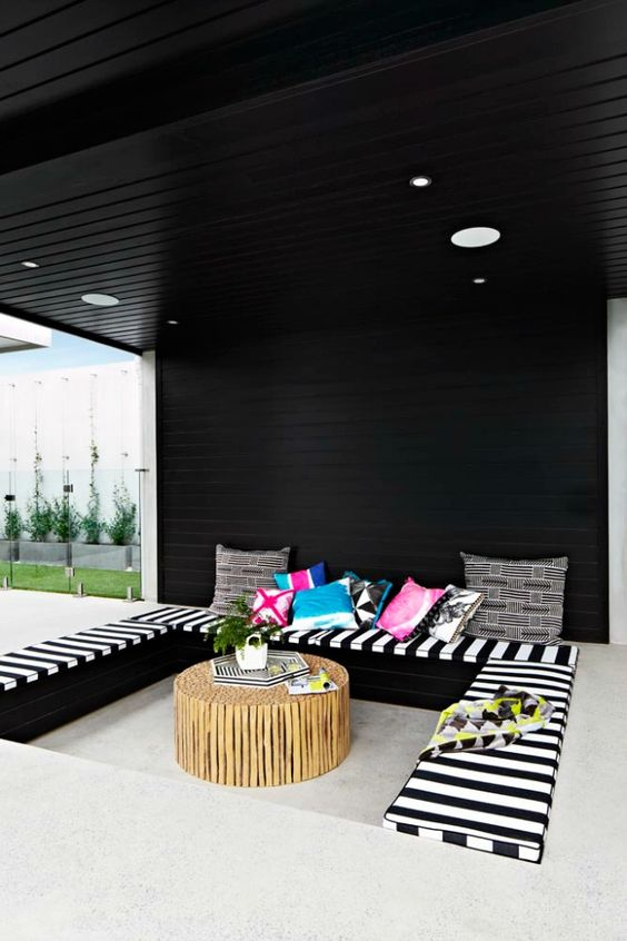 colorful conversation pit with striped cushions and a wooden coffee table