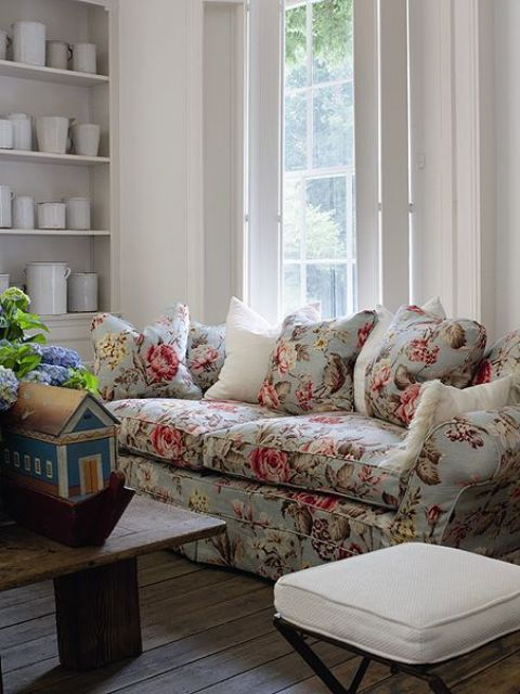 vintage-inspired grey sofa with cushions and pillows and subtle pink flowers