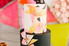 17 a black and colorful geometric cake with an edible topper