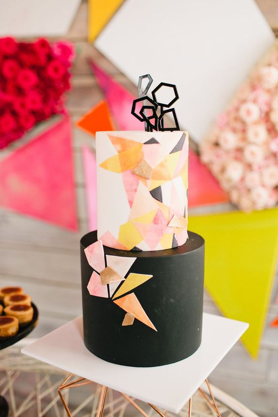 a black and colorful geometric cake with an edible topper